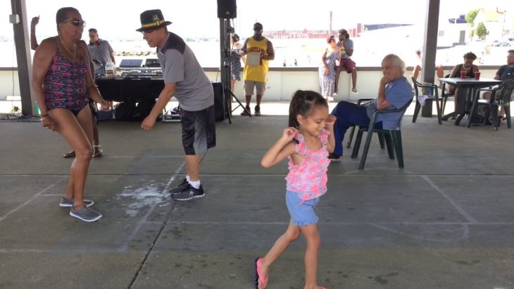 Little girl joins small group of dancers at Reggae on West Beach in New Bedford